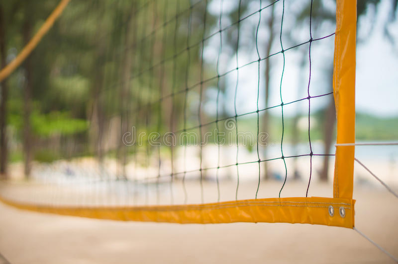 Corner of yellow voleyball net on beach among palm trees stock photos