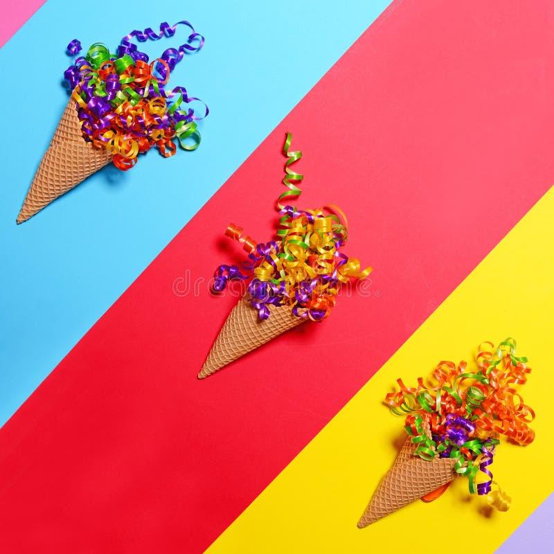 Cornets de crème glacée avec les confettis colorés sur le fond coloré - configuration plate photo stock