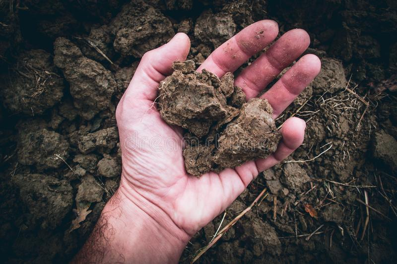 Human male hand with fertile soil moody style image. Human male hand with fertile soil - moody style image stock photo