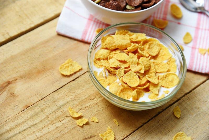 Cornflakens i bunke med mjölkar på träbakgrund för sädes- sund frukost royaltyfria foton