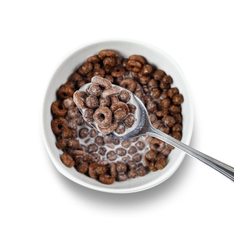 Cornflakes de chocolat dans une cuillère au-dessus d'un plat Fin vers le haut Vue supérieure D'isolement sur le fond blanc photographie stock