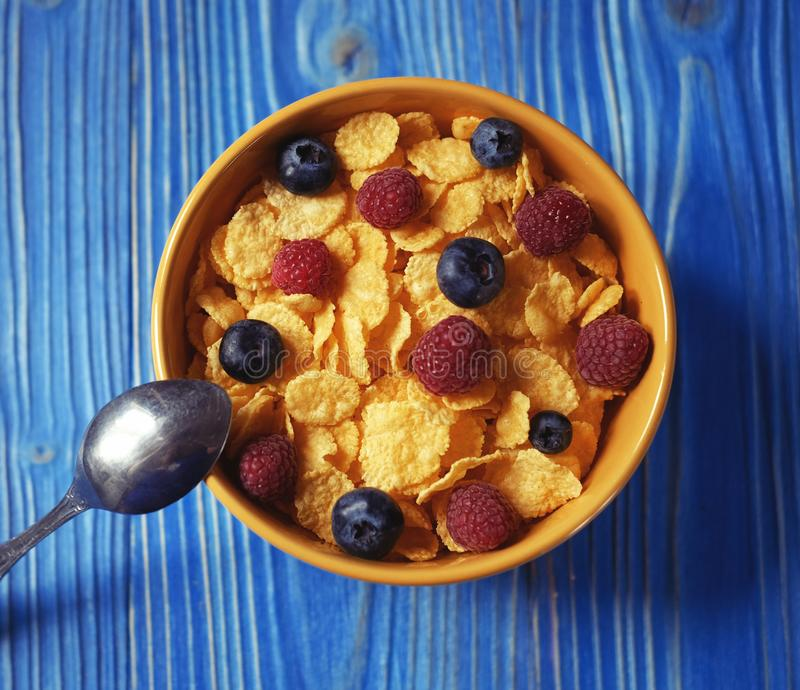 Cornflakes and different Berries - Blueberries and fresh Raspberries, blue wooden background. Good breakfast. Cornflakes and different Berries - Blueberries and royalty free stock images