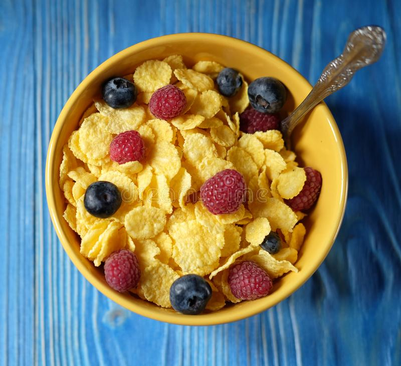 Cornflakes and different Berries - Blueberries and fresh Raspberries, blue wooden background. Good breakfast stock images
