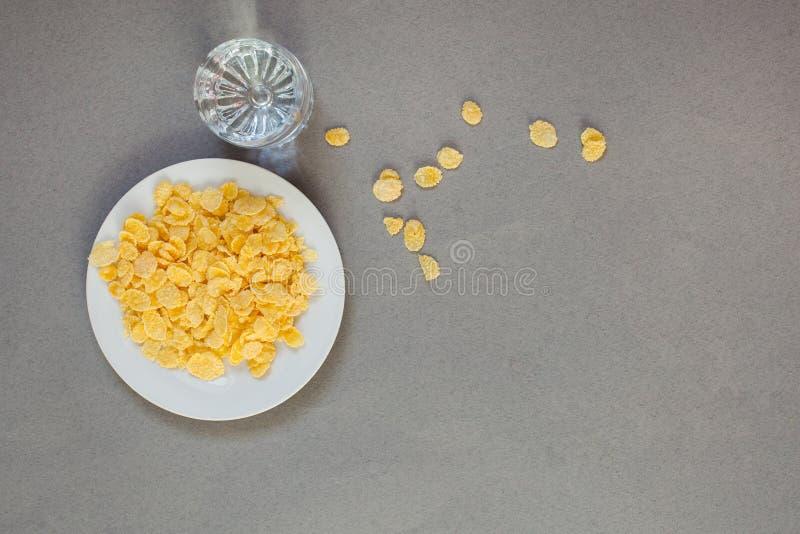 Cornflakes in een witte kop en een glas met water op een grijze achtergrond, esthetica van chaos stock foto