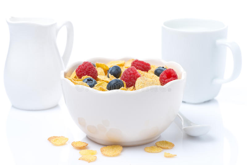 Cornflakes with fresh berries in a bowl and milk, isolated royalty free stock photo