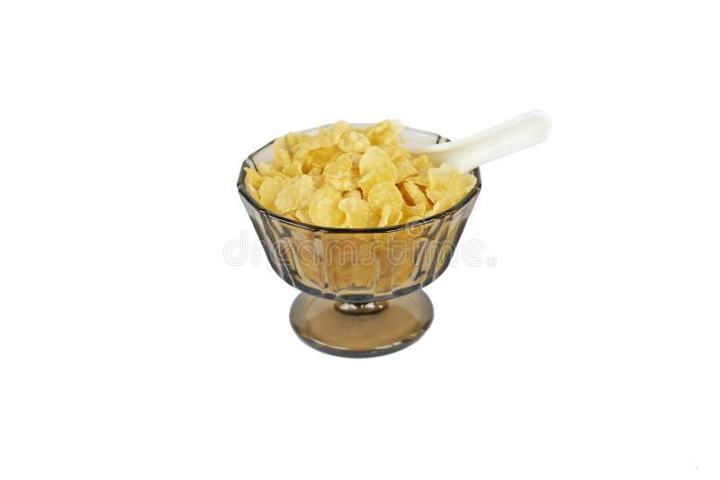 Cornflakes i en brunaktig traditionell glass bunke med ställningen och en vit kinesisk skedhalva som begravas i cornflakens royaltyfri bild