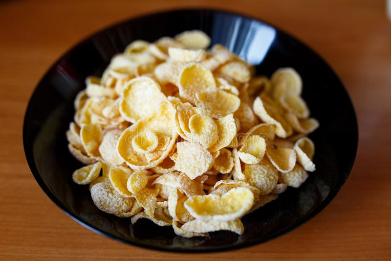 Cornflakes i en svart bunke Sund mat i morgonen arkivfoton