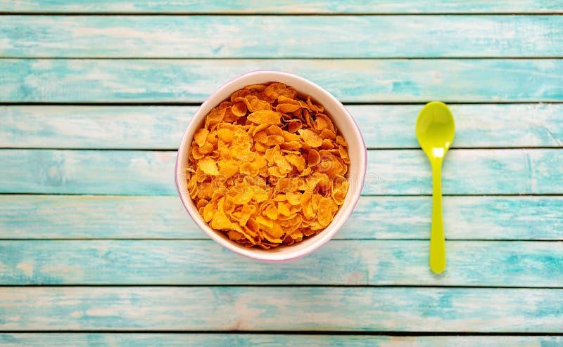 Cornflakes pyskują na rocznika drewnianym stole ?y?ka ?ywno?? organiczna zdjęcia stock