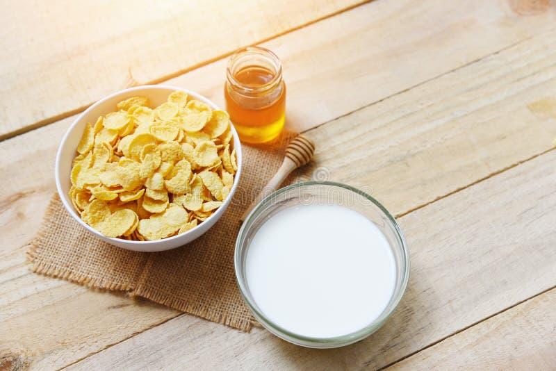 Cornflakes w pucharze z mlekiem i miodem w słoju na drewnianym tle dla zboża zdrowego karmowego śniadania obrazy stock