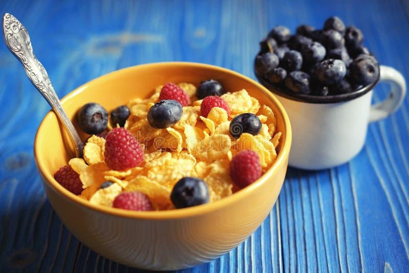 Cornflakes z jagod czarnymi jagodami na błękicie i malinkami zalecają się obrazy stock