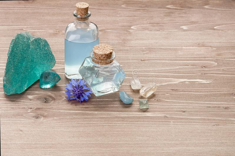 Cornflower flower blue water in glass bottles, natural stones and flowers on brown wooden background, copy space. Aromatherapy or stock photography