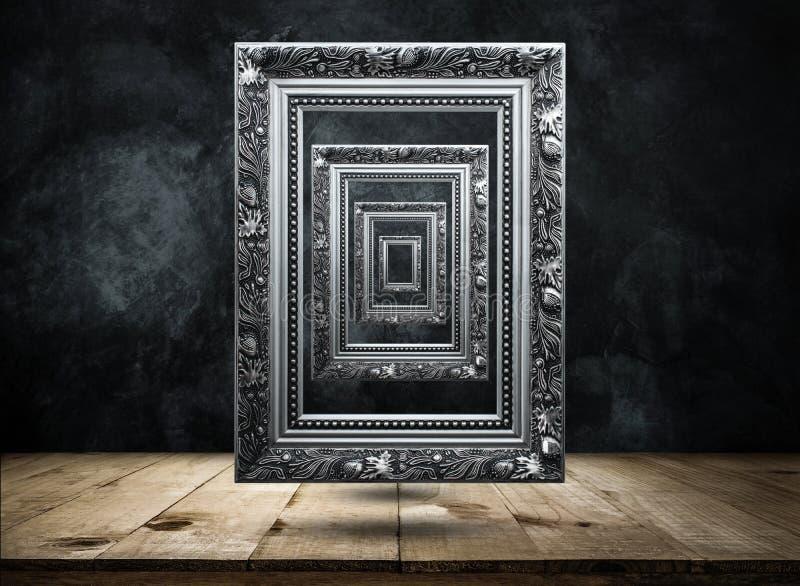 cornice antica d'argento sulla parete scura di lerciume con la linguetta di legno immagini stock
