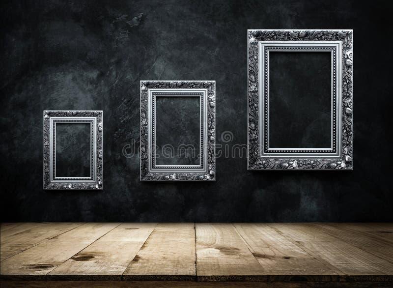 cornice antica d'argento sulla parete scura di lerciume con la linguetta di legno fotografia stock