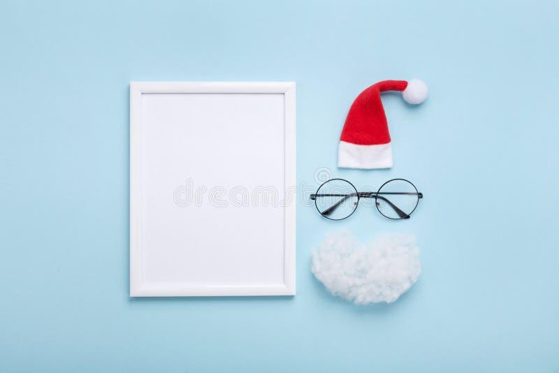 Cornice, cappello di Santa, barba e vetri sulla vista superiore del fondo blu Modello creativo di natale Cartolina d'auguri o inv immagine stock