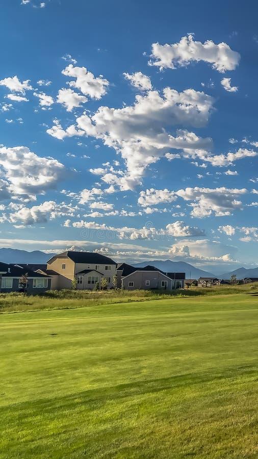 Cornice verticale Fairway di un campo da golf in vista di case e montagne sullo sfondo immagini stock libere da diritti
