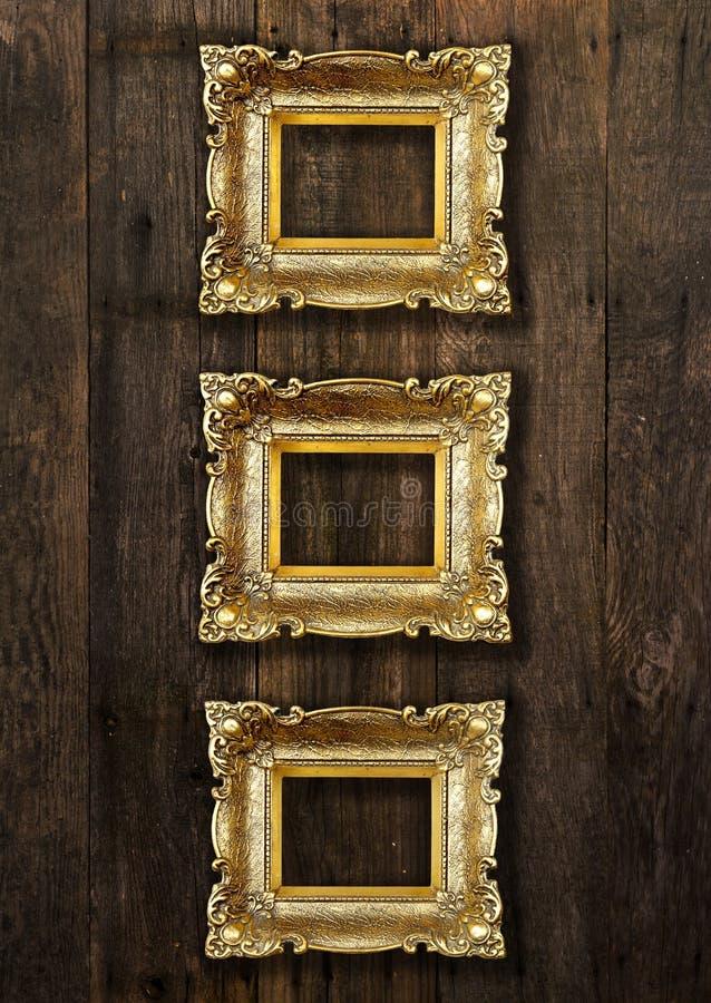 Cornici del vecchio oro sulla parete di legno immagini stock