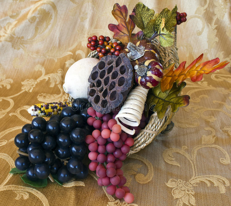 Cornicopia on a Gold Brocade table cloth. With grapes, leaves, gourds, seed pods royalty free stock photography