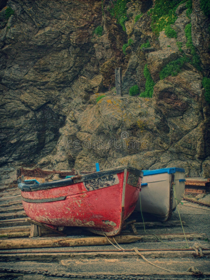 Two small Cornish fishing boats on a small cove. Two small fishing boats waiting to be taken out to sea from a small sheltered cove royalty free stock photography