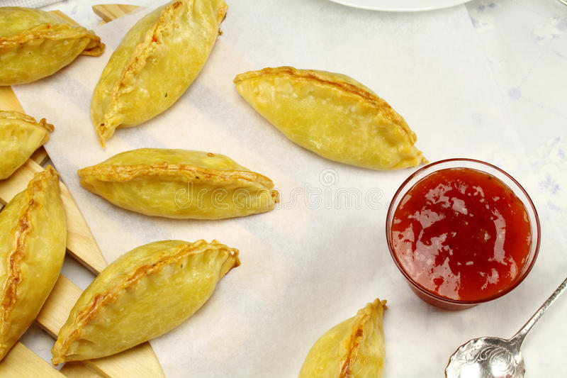 Cornish Pasties. Delicious fresh baked golden pasties with sweet chili relish stock images