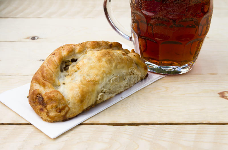 Cornish pasty. A traditional Cornish past on a wooden table with a pint royalty free stock photography