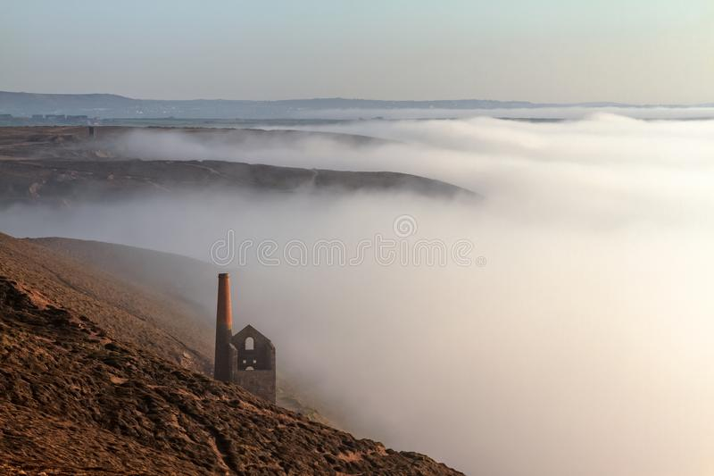 Cornish Tin Mine in Sea Mist. A Cornish tin mine being engulfed by the sea mist at St.Agnes head, Cornwall stock images