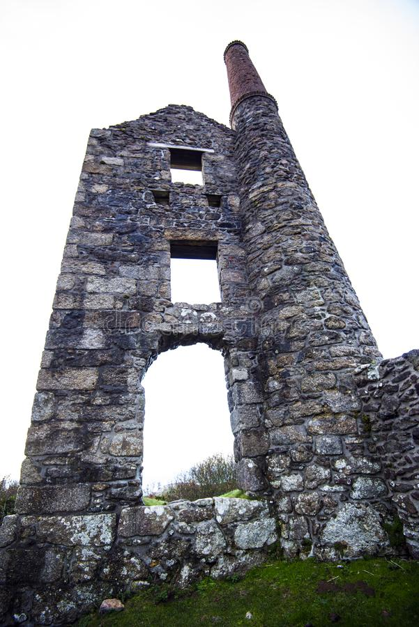 Cornish Tin Mine ruins - Cornwall, England. This iconic image of the ruins of a Tin Mine ventilation shaft and pump engine house reflects the end of the tin royalty free stock image