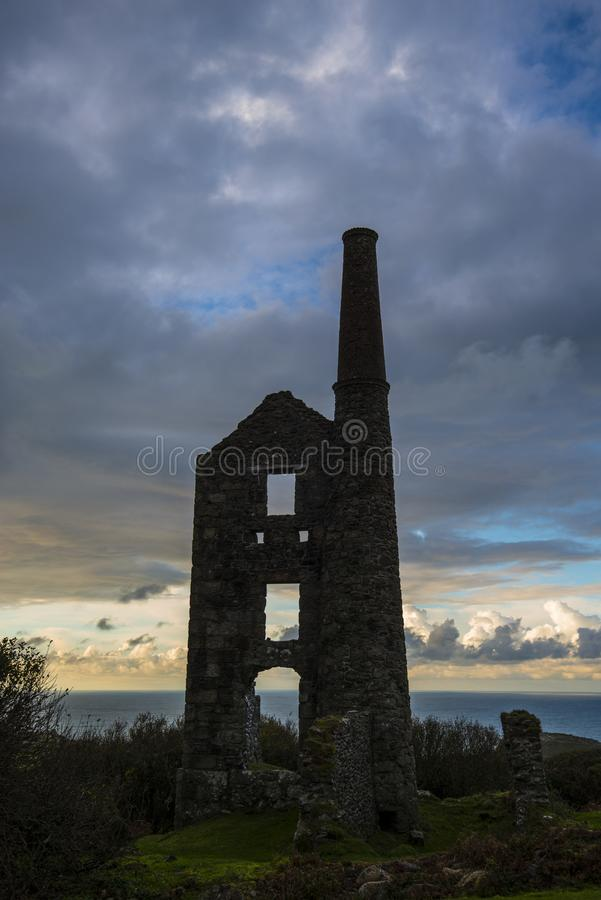 Cornish Tin Mine silhouette at sunset - Cornwall, England. This iconic image of the ruins of a Tin Mine ventilation shaft and pump engine house reflects the end royalty free stock images