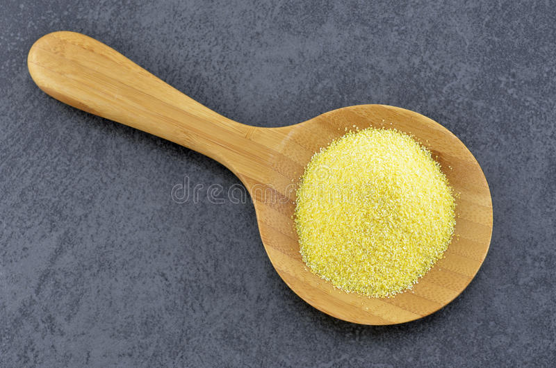 Cornmeal. In wooden spoon on slate background royalty free stock photos