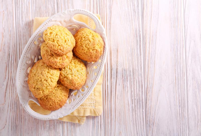 Cornmeal biscuits in a plate. On wooden table royalty free stock photo