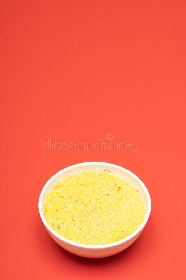 Cornmeal a bowl. On a colored background stock photos