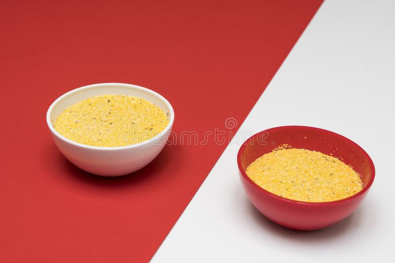 Cornmeal a bowl. On a colored background stock images