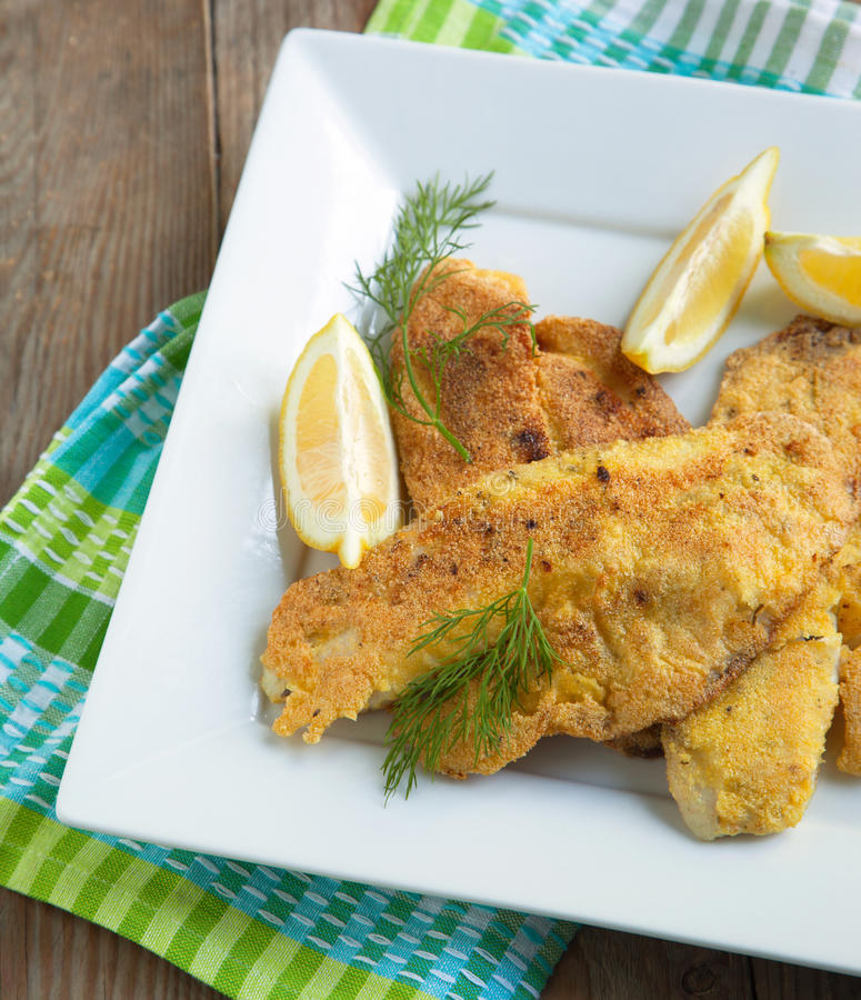 Cornmeal-crusted tilapia. Served in plate with lemon royalty free stock photography