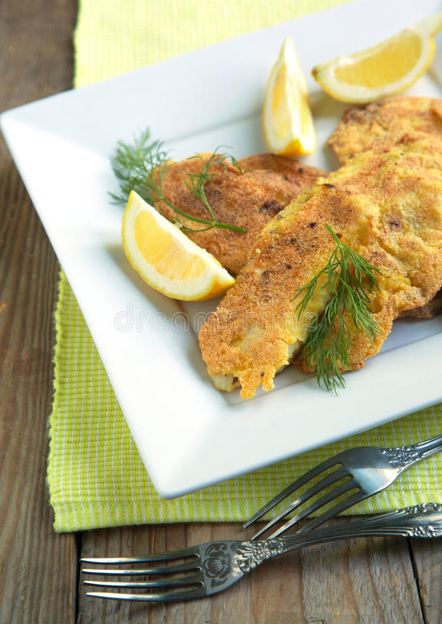 Cornmeal-crusted tilapia. Served in plate with lemon stock photos