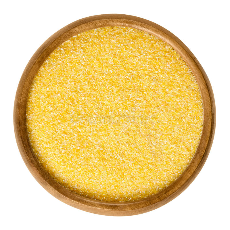 Cornmeal medium in wooden bowl over white. Cornmeal in wooden bowl. Raw uncooked meal, medium ground from dried maize. Common stable food. Boiled cornmeal is royalty free stock photography