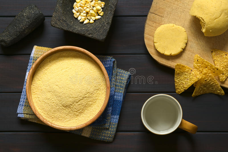 Cornmeal. Overhead shot of cornmeal in wooden bowl with corn kernels in mortar, cup of water and cornmeal dough on wooden board, photographed on dark wood with royalty free stock image