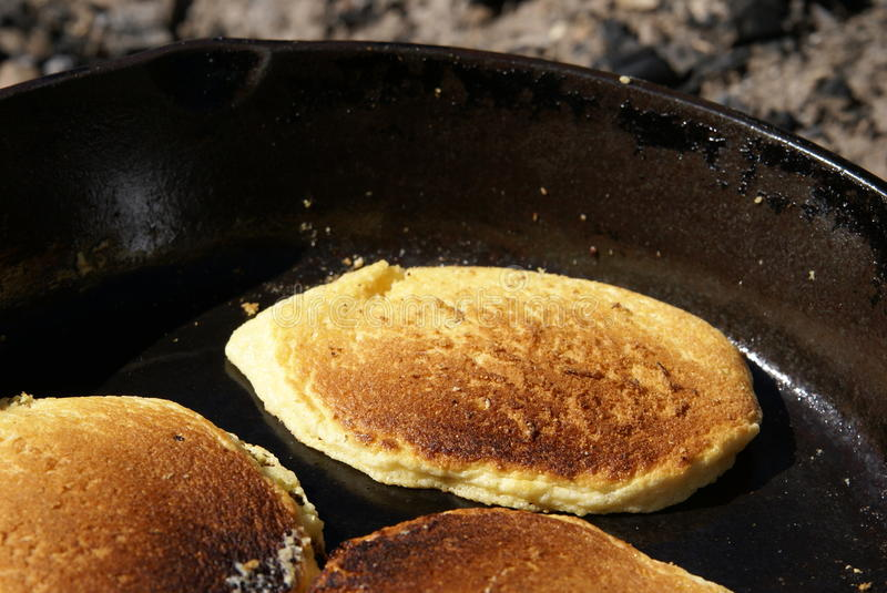 Cornmeal Pancakes. Cooking in a cast iron skillet over an open fire outdoors. Close up view of cakes royalty free stock photos