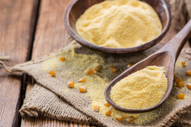 Cornmeal (on rustic background). Portion of Cornmeal (on rustic background) as detailed close-up shot royalty free stock photos
