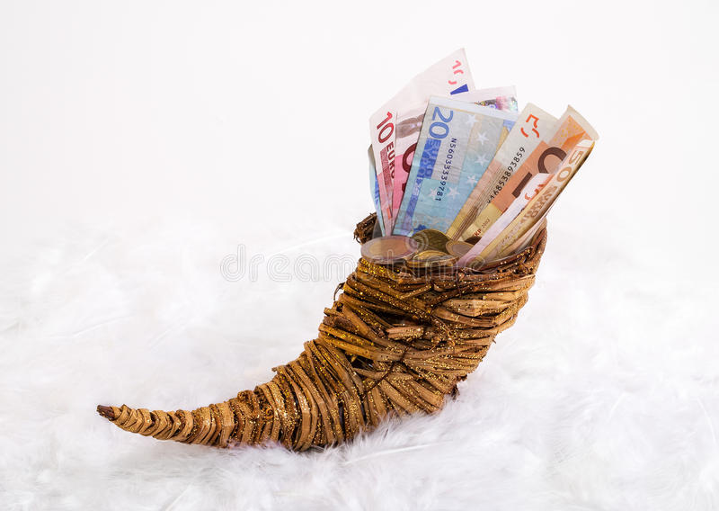 Cornucopia - bills and change in a horn of plenty. Horn standing on a bed of feathers royalty free stock photos