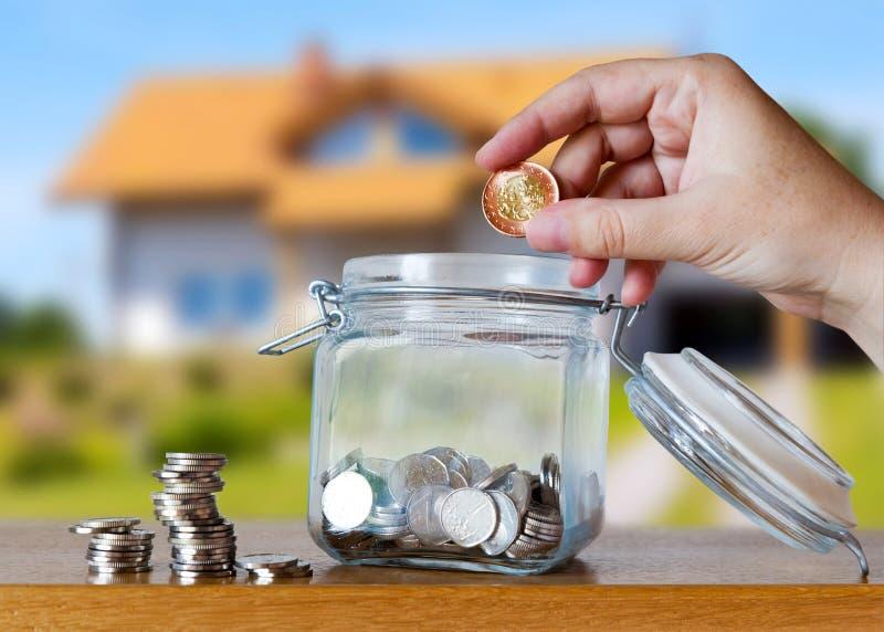 A coroa checa inventa em um moneybox de vidro - economias para a prestação do custo ou da hipoteca da casa fotografia de stock