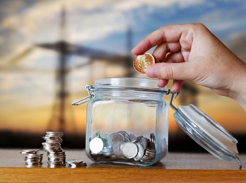 A coroa checa inventa em um moneybox de vidro - economias para a prestação do custo ou da hipoteca da casa foto de stock