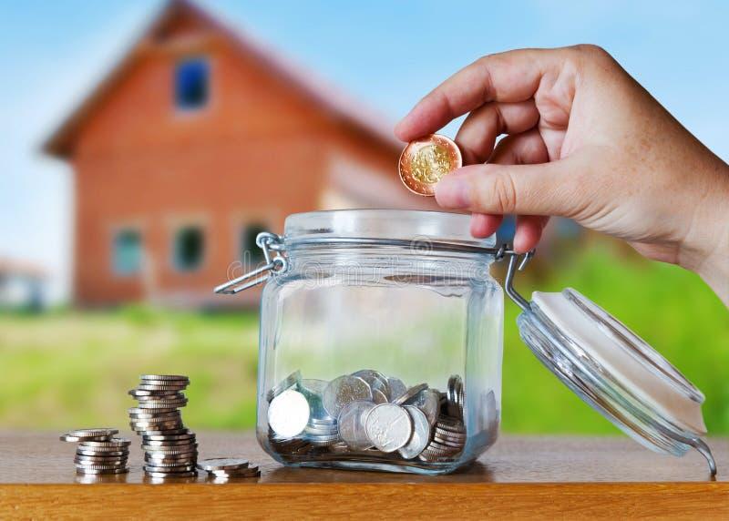 A coroa checa inventa em um moneybox de vidro - economias para a prestação do custo ou da hipoteca da casa imagem de stock