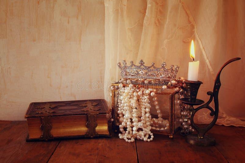 Coroa da rainha do diamante, pérolas brancas ao lado do livro velho imagens de stock royalty free