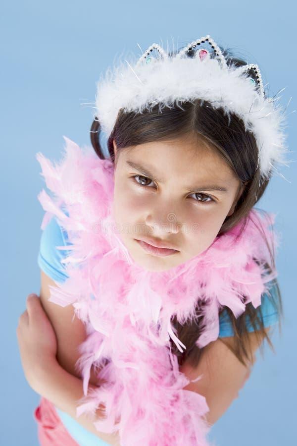 Coroa da rapariga e boa de pena desgastando que olha de sobrancelhas franzidas imagem de stock