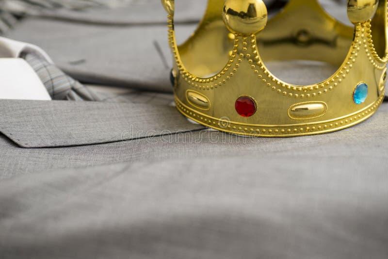 Coroa do ouro que encontra-se no terno de um homem de negócios Conceito do negócio metaphor fotos de stock royalty free