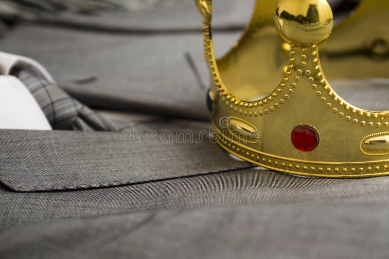 Coroa do ouro que encontra-se no terno de um homem de negócios Conceito do negócio metaphor fotos de stock