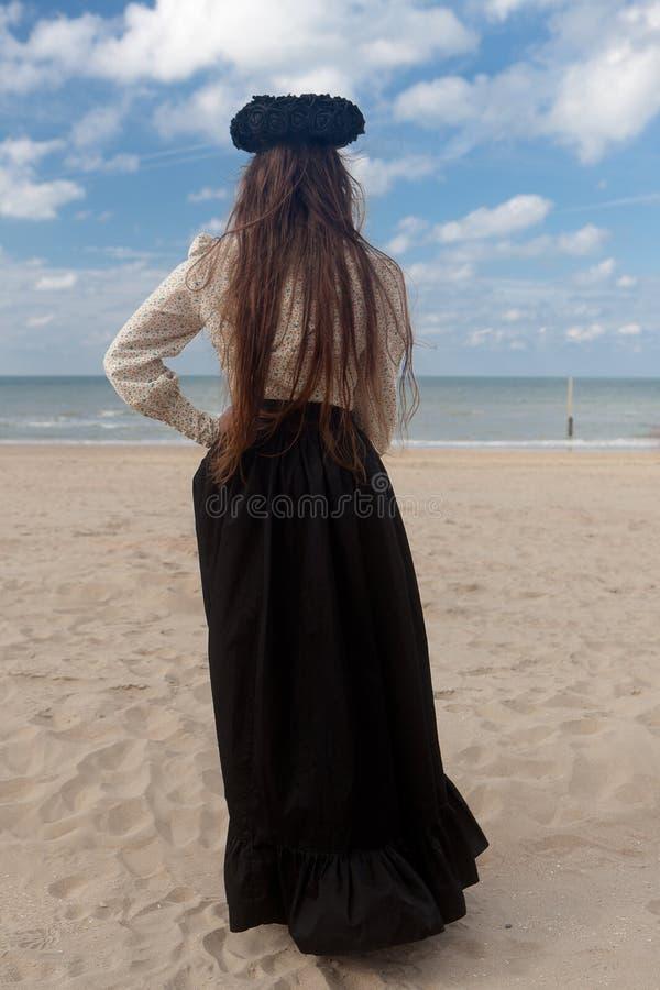 Corona color de rosa del negro trasero de la playa de la mujer, De Panne, Bélgica foto de archivo libre de regalías