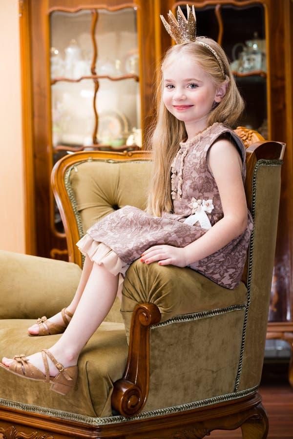 Corona d'uso dei capelli biondi della bambina che sta alla sedia fotografia stock
