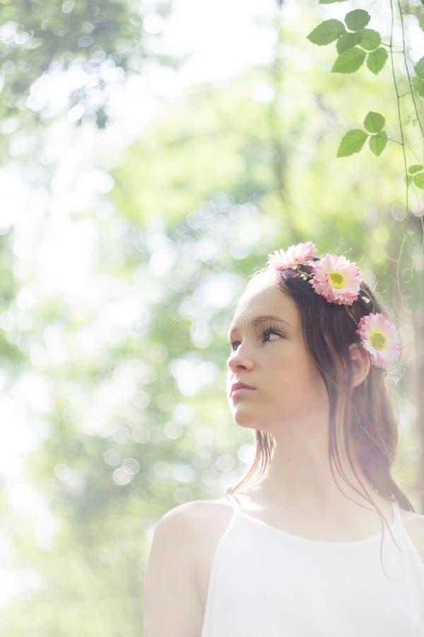 Corona d'uso del fiore della bella ragazza preteen caucasica e vestito bianco nel fondo leggiadramente della foresta Ritratto di  immagini stock libere da diritti