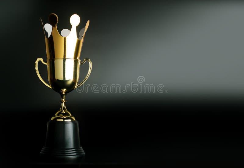 Corona de oro de la cartulina encima del trofeo de oro del campeón foto de archivo libre de regalías