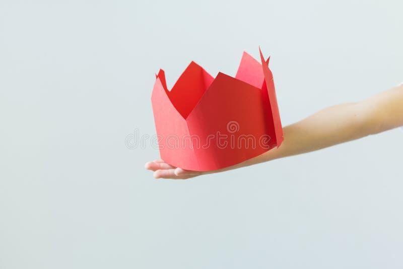 Corona de papel falsa en manos del muchacho Concepto de la caricatura fotos de archivo libres de regalías